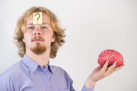 Young guy playing with human brain model. Man discovering innovation and thinking having question mark on his head.