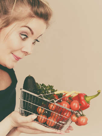 Buying good food, vegetarian products. Positive funny woman holding shopping basket with green red vegetables inside, recommending healthy high fibre diet, lifestyle modification, on grey Archivio Fotografico