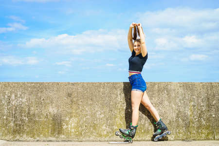 Young woman wearing roller skates outdoor. Fashionable fit girl having fun at sunny summer day. Stock Photo