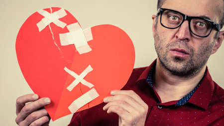 Bad relationships, breaking up, sadness emotions concept. Adult man holding broken heart, on grey Stock Photo