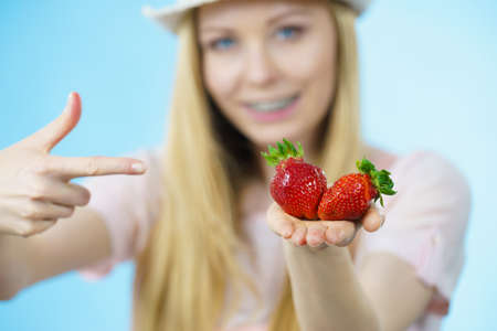 Young woman showing fresh strawberries fruits on blue. Healthy meal. Stock Photo