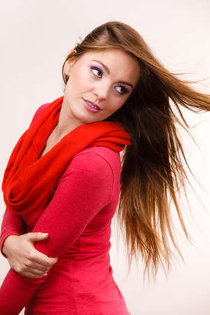 Woman fashionable girl wearing red clothing posing in studio with wind in long healthy straight hair Stock Photo