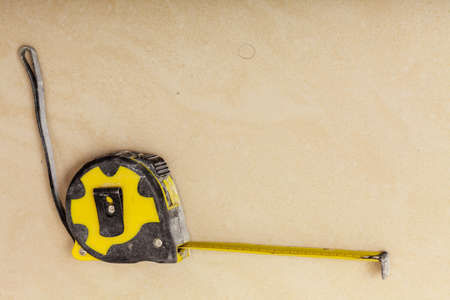 Crafting, tinkering objects. Black and yellow measuring tape lying on brown floor.