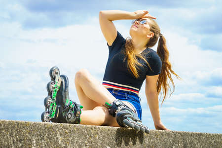 Mujer joven con patines al aire libre. Chica de moda ajuste divirtiéndose descansando en un día soleado de verano. Foto de archivo
