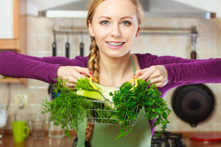 Buying healthy dieting food concept. Woman in kitchen having many green vegetables holding small shopping basket trolley.