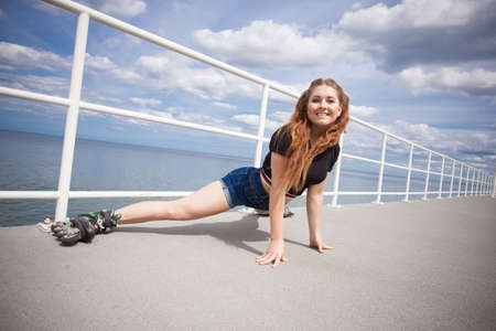 Happy joyful young woman wearing roller skates fooling around stretching her legs. Female being sporty having fun during summer time near sea. Stock Photo
