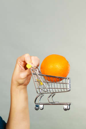 Buying healthy food, vegetarian, gluten free, vegan products. Woman holding shopping cart with orange inside