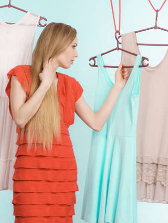 Young blonde long hair woman in clothes shop store picking summer outfit, dresses hanging on clothing hangers, on blue. Sale shopping concept