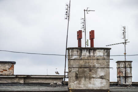 Roof of tenement house with many antennas and chimneys during cloudy day.
