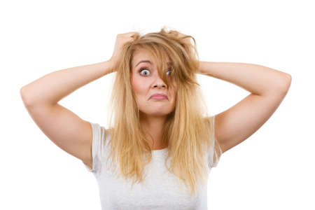 Bad hairstyle concept. Crazy, mad blonde woman with messy hair looking stressed out. Studio shot on white background. Stock Photo