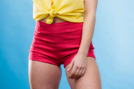 Closeup of alluring woman hips. Slim girl wearing yellow shirt and red shorts on blue. Summer fashion. Stock Photo