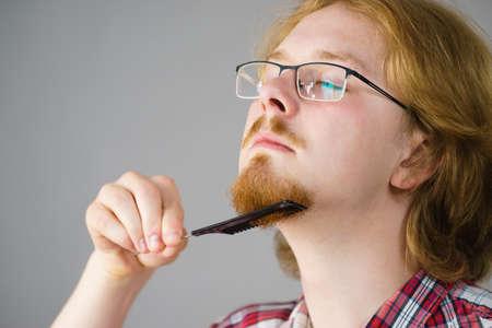 Ginger nerd man brushing his beard using comb taking care of facial hair. 写真素材
