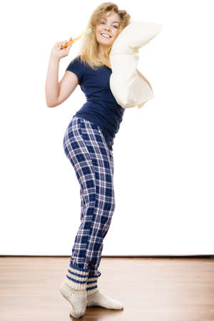 Happy cheerful woman wearing blue pajamas holding pillow and toothbrush, sleep outfit blue tshirt and checked trousers