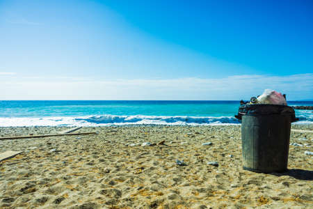Gray metal garbage bin or trash can with a plastic bag inside beach outdoor Standard-Bild