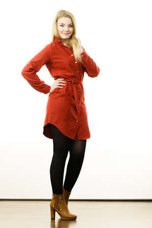 Fashionable woman wearing long red vintage dress, black leggings and brown high heels boots. Autumnal outfit concept.
