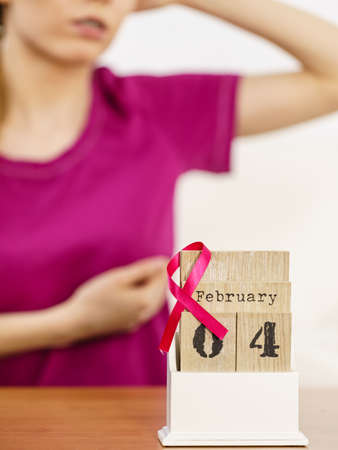 Woman and calendar, it is 4 february world breast cancer day, date with pink awareness ribbon. Healthcare and medicine concept.