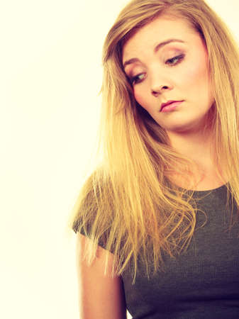 Face expression, emotions concept. Sad cute young blonde attractive woman in dark t shirt. Foto de archivo