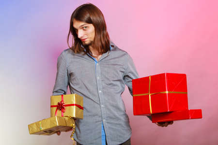 Holiday, xmas winter time season and special occasion. Young handsome stylish man holding a lot of presents gifts boxes