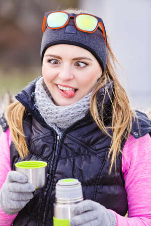 Woman traveler girl wearing warm sporty clothes outdoor in cold weather drinking hot tea from vacuum flask thermos, warming up, making silly face.