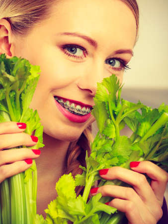 Woman in kitchen holding green fresh stemmed celery. Young housewife cooking. Healthy eating, vegetarian food, dieting and people concept.