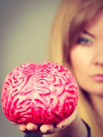 Blonde woman holding brain having something on mind, thinking of solution idea. Stock Photo