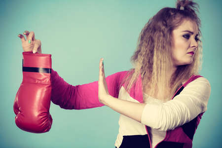 Young woman looking with disgust at boxing glove, she does not like fighting and aggression