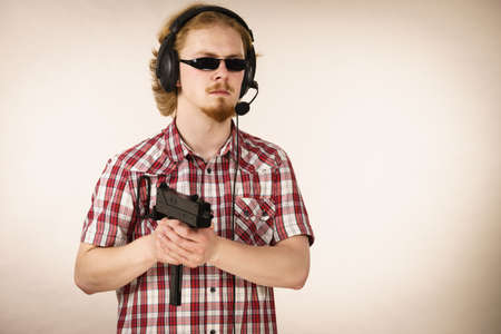 Nerd geek young adult man playing on the video console holding gun wearing headphones with microphone. Gaming gamers concept.
