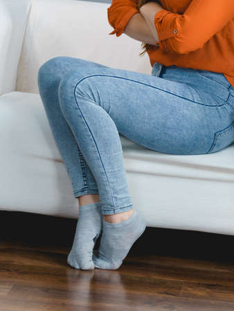 Unrecognizable woman wearing tight skinny fit slim light blue jeans and grey short socks.