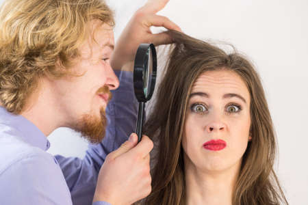 Man looking at woman hair roots using magnifying glass. Guy having doubts about trichology Stock Photo
