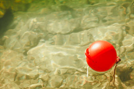 One lonely red ball buoy on water captured high angle view outdoor.