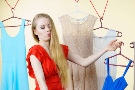 Young blonde long hair woman in clothes in shop or wardrobe choosing summer outfit, dresses hanging on clothing hangers. Sale shopping fashion and style concept