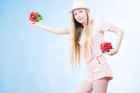 Positive teenage blonde long hair girl wearing summer clothing sun hat holding two bunches of fresh radish, on blue