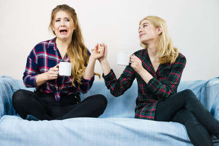 Two women spending time together on sofa drinking tea. Female complaining, the other one comforting her. Perks of friendship.