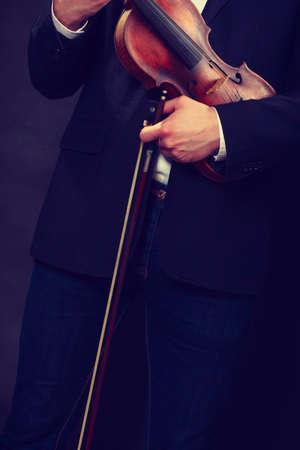 Music passion, hobby concept. Man man dressed elegantly holding wooden violin. Studio shot on dark background