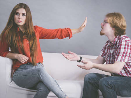 Man begging woman who is sitting on sofa for forgiveness. Couple after fight or argue. Female showing speak to hand Stock Photo