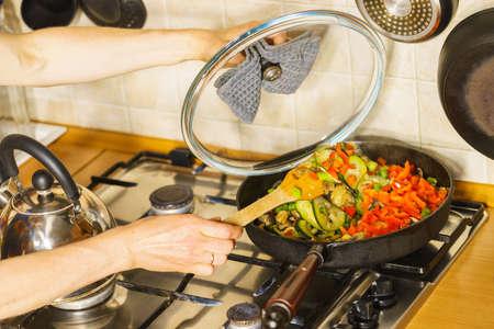 Dieting eating, preparing food concept. Many chopped healthy vegetables on frying pan, vegetarian meal preparation.