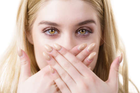 Close up of young blonde woman showing silence gesture hiding her mouth being hands. Stock Photo