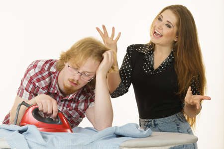 Woman being happy while her bored man is doing household duties, ironing.