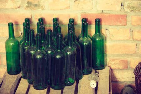 Empty green wine bottles in the wooden shelf in cellar