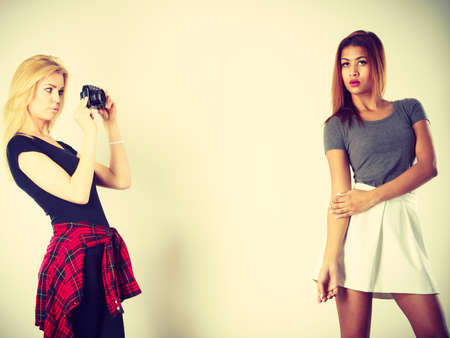 Photographer and model. Blonde girl shooting images, taking photos with camera, photographing mulatto female model