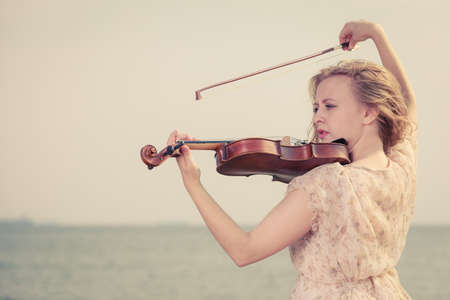 Music love, hobby and everyday passion concept. Woman on beach near sea playing on violin 版權商用圖片