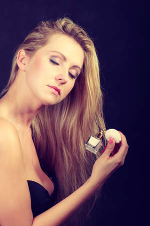 Beautiful elegant blonde woman with necklace holding and applying perfume after shower, studio shot on dark background