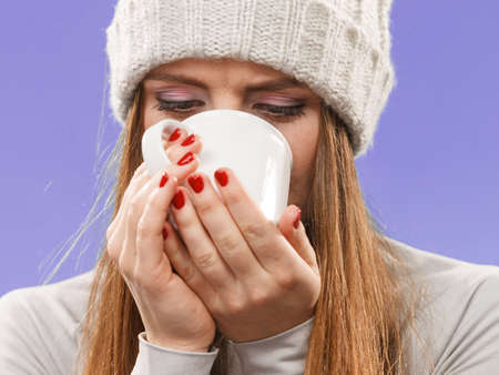 Attractive woman long hair girl in winter wool cap holds mug with tea hot beverage, warming herself studio shot on violet. Stock Photo
