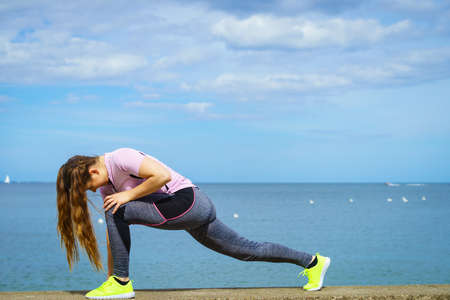 Super fit attractive young woman wearing fashionable outfit working out being active outside during sunny weather. Stretching her legs or practice yoga next to sea