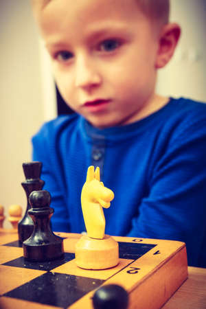 Intelligent, smart ass kids, games good for brain intelligence concept. Young kid boy playing chess and having fun.