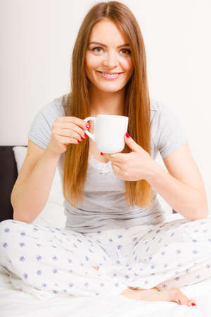 Morning, awakening drink concept. Beautiful smiling young woman holding a cup of hot coffee or tea in bed indoor.