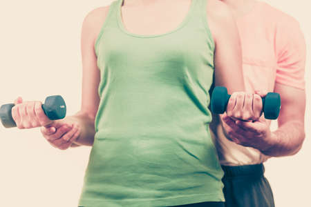 Couple fit woman and strong man exercising with dumbbells. Muscular guy and fitness girl lifting weights. Bodybuilding.