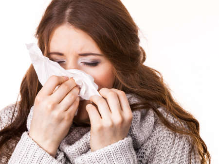 Sick freezing woman sneezing in tissue. Girl wearing warm sweater being cold and trembling. Flu or other virus. Health care. Stock Photo