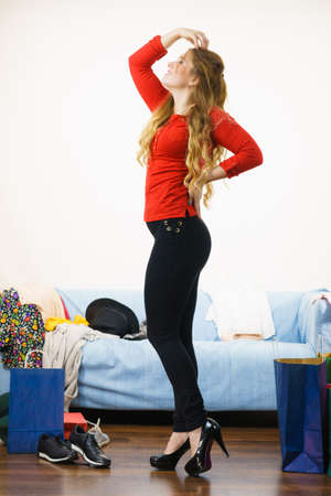 Beautiful woman posing presenting fashionable outfit. Female wearing red top with long sleeve, tight slim black jeans trousers and dark high heels.