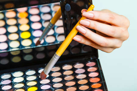 Cosmetic beauty procedures and makeover concept. Woman holds makeup professional eye shadows palette and brush. Make up applying. Stockfoto